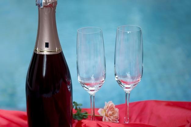 Champagne und zwei leere gläser mit rosenblüte