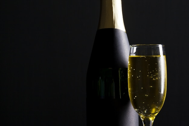Champagne-weinglas und -flasche auf schwarzem