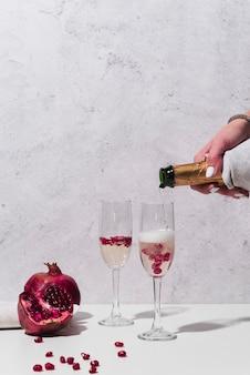 Champagner, der in glas mit granatapfel gießt
