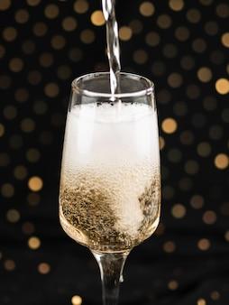 Champagner, der in glas mit schaum gießt