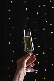 Champagner in der hand der frau auf einer schwarzen oberfläche mit bokeh