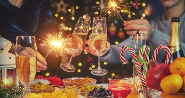Champagner in der hand gegen den weihnachtsbaum