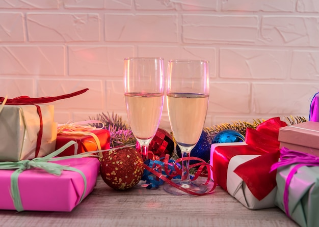 Champagner in gläsern auf holztisch mit bunten weihnachtsgeschenken