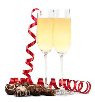 Champagner in gläsern, rotes band und schokolade isoliert auf weiß