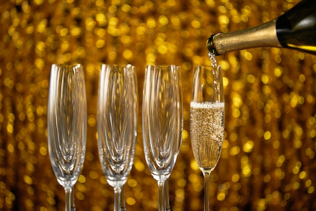 Champagner in glas auf goldener stilvoller farbe gießen