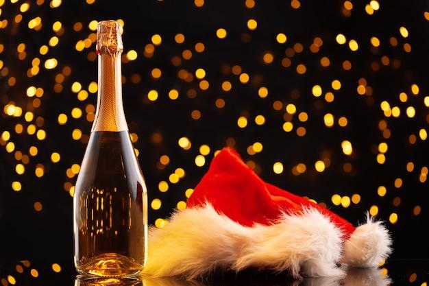 Champagner- und weihnachtsmannhut auf unscharfem girlandenhintergrund