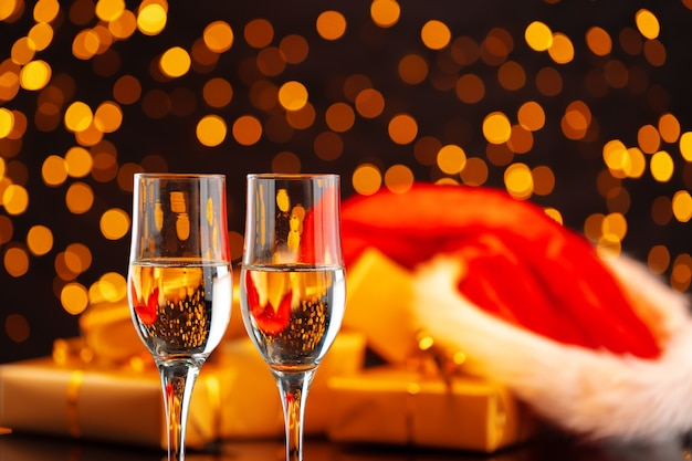 Champagner und weihnachtsmannhut auf unscharfer girlandenhintergrund-vorderansicht