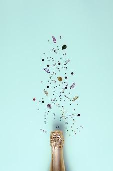 Champagner-weinflasche mit goldenen konfetti-sternen auf blauem tischhintergrund