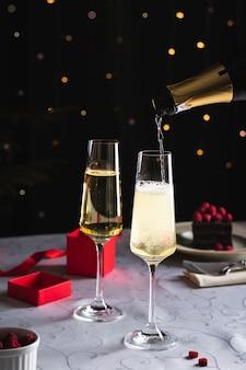 Champagner wird in ein glas neben einem anderen glas gegossen