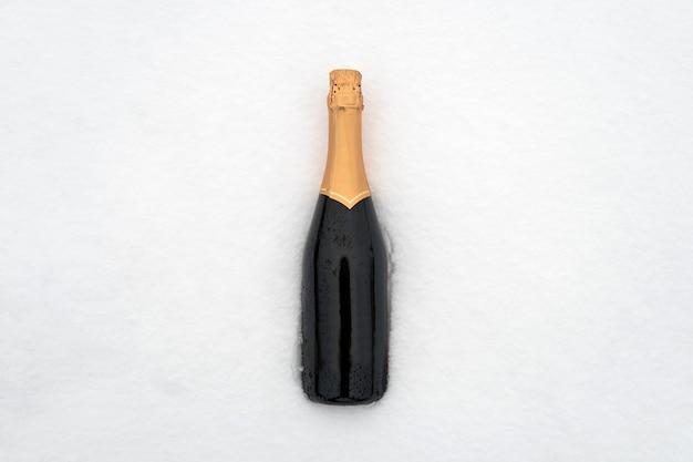 Champagnerflasche im schnee. grüne geschlossene flasche ohne etikett.