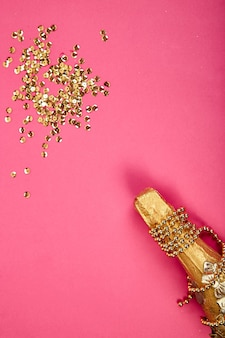 Champagnerflasche mit goldenem konfetti auf rosa papierhintergrund