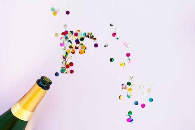 Champagnerflasche mit hellem konfetti auf einem rosa hintergrund