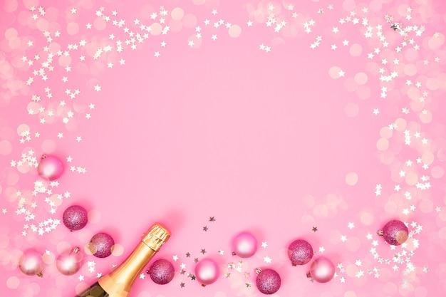 Champagnerflasche mit weihnachtsdekorationen auf rosa hintergrund. flache lage von weihnachten, jubiläum, neujahrsfeierkonzept.
