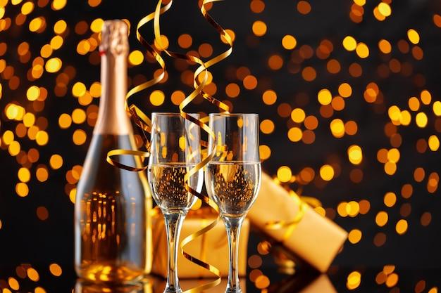 Champagnerflasche und verpacktes geschenk auf unscharfem girlandenhintergrund