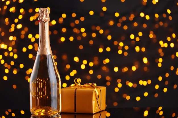 Champagnerflasche und verpacktes geschenk auf unscharfem hintergrund der vorderansicht der weihnachtsbeleuchtung