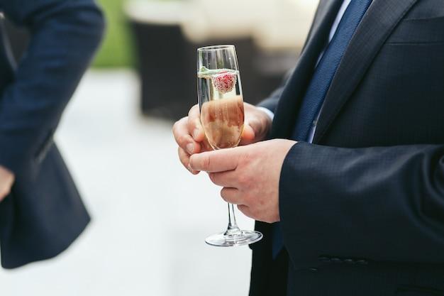 Champagnerflöte von einem mann in schwarzer jacke gehalten