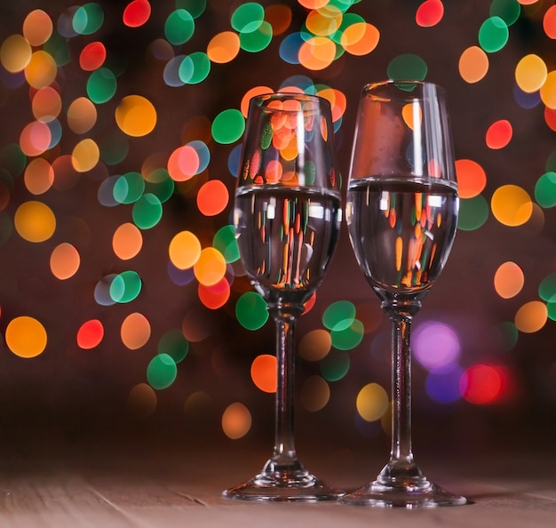 Champagnergläser auf dem hintergrund der weihnachtsbeleuchtung.