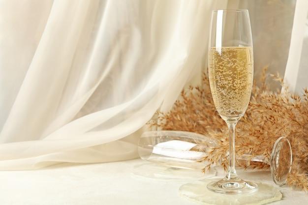 Champagnergläser, epoxidharz und feldblumen auf weißem tisch