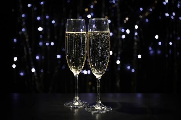 Champagnergläser gegen dunklen raum mit verschwommenen lichtern, kopierraum