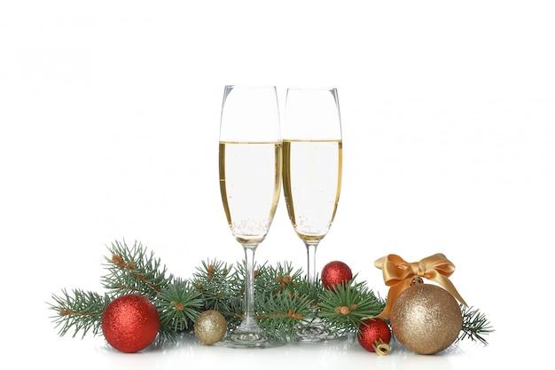 Champagnergläser, kugeln und tannenzweige isoliert auf weißem raum