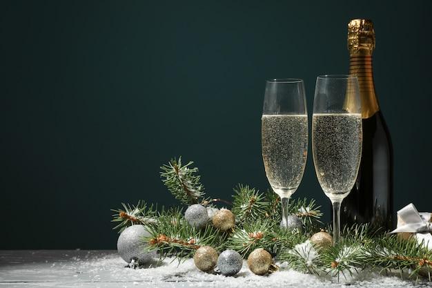 Champagnergläser und flasche auf dekoriertem raum, platz für text