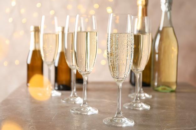 Champagnergläser und flaschen auf dekoriertem raum, platz für text