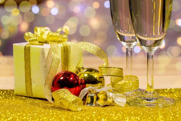 Champagnergläser werden zusammen mit einer geschenkbox und glänzenden kugeln platziert. platz oben rechts für ihre formulierung.