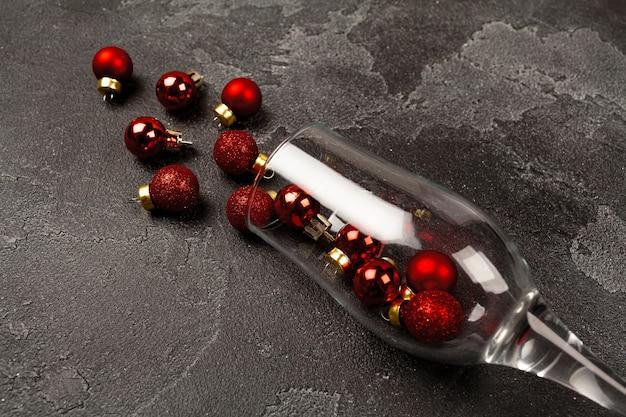 Champagnerglas mit kleinen weihnachtskugeln verstreute draufsicht