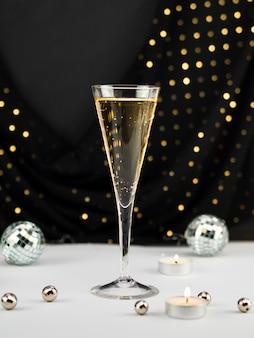 Champagnerglas mit kugeln und kerze