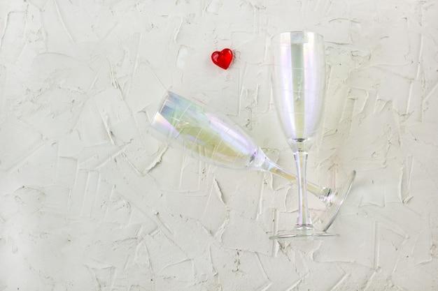 Champagnerglas mit rotem herzen auf weißem hintergrund. draufsicht, kopierraum.