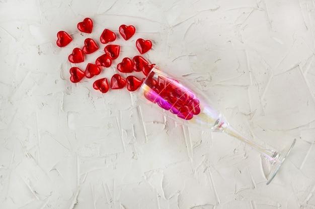 Champagnerglas mit spritzer des roten herzens auf weißem hintergrund. draufsicht, kopierraum. valentinstag konzept
