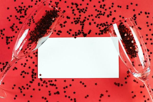 Champagnerglas mit sternförmigen pailletten auf einem roten hintergrund mit kartenrohling. party-, weihnachts-, neujahrs- und valentinstagfeierkonzept. banner. draufsicht. flach liegen.