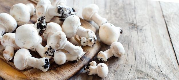 Champignon-pilze auf einem alten holztisch