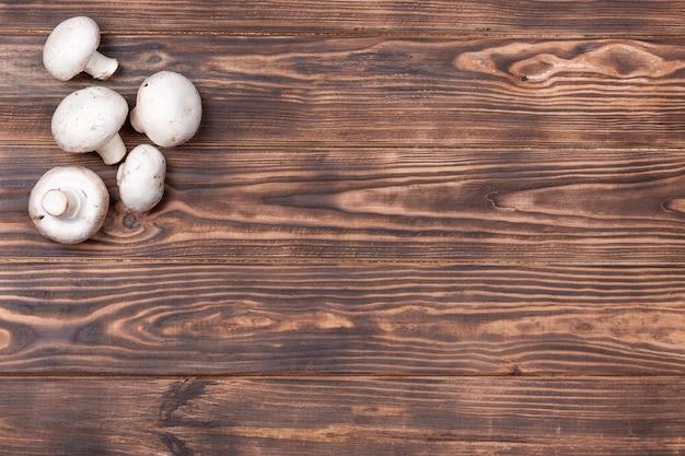 Champignon-pilze auf vintage rustikalem holztisch hintergrund extreme nahaufnahme