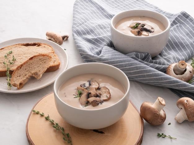 Champignoncremesuppe in der weißen schüssel mit brot auf dem tisch. leckere cremesuppe mit champignons.