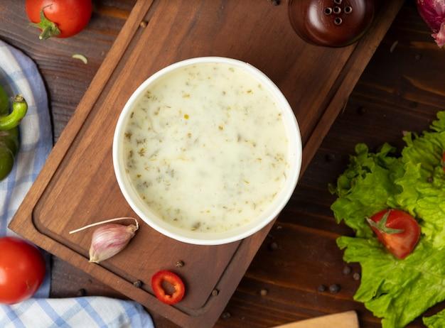 Champignoncremesuppe in einwegbecherschale, serviert mit grünem gemüse.