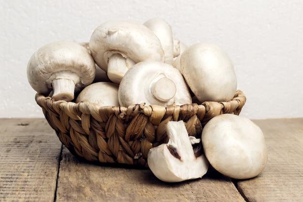 Champignons champignons in einem weidenkorb im rustikalen stil