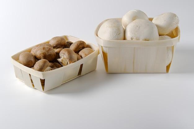 Champignons der weißen und braunen pilze im hölzernen korb auf hellem hintergrund.