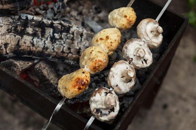 Champignons werden am spieß gegrillt. picknick in der natur. vegetarisch und vegan.