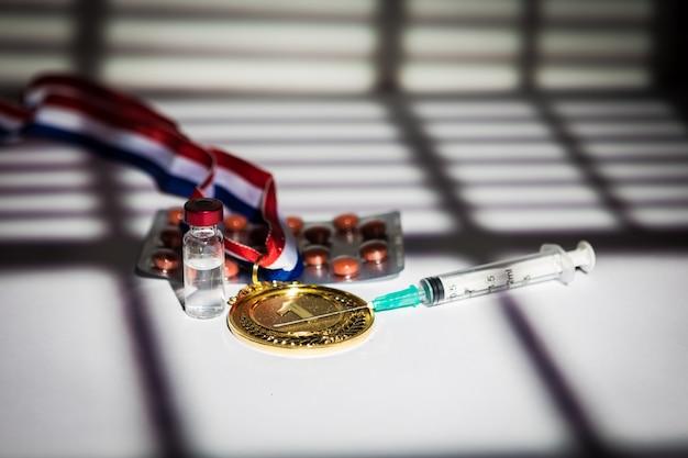 Champion goldmedaille, dopingmittelspritze, tablettentablette und fläschchen mit verbotenen substanzen mit licht und schatten eines vorhangs, der durch das fenster eindringt. sport- und dopingkonzept