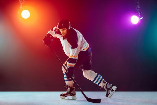 Champion. männlicher hockeyspieler auf eisplatz und dunklem neonfarbenem hintergrund mit taschenlampen. sportler in der ausrüstung, helmübungen. konzept des sports, des gesunden lebensstils, der bewegung, des wellness, der aktion.