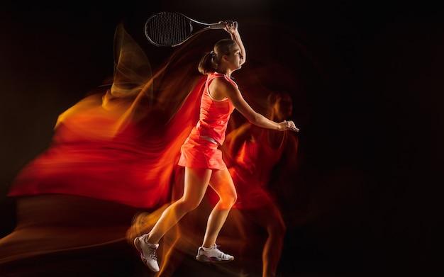 Champion. professionelles weibliches tennisspielertraining isoliert auf schwarzem studiohintergrund in gemischtem licht. frau im sportanzug üben. gesunder lebensstil, sport, training, bewegung und aktionskonzept.