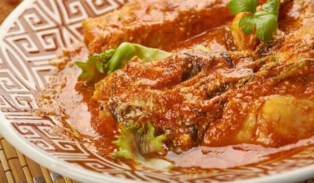 Chana aur khatte pyaaz ka murgh - indische hühnchenhäppchen mit eingelegten schalotten und kichererbsensauce, serviert mit parantha