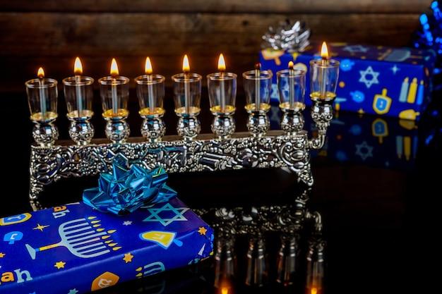 Chanukka-hintergrund mit brennender menora und geschenkboxen. jüdischer feiertag.