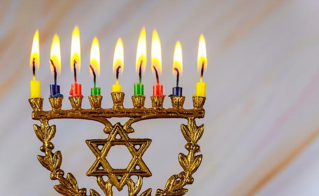 Chanukka menora mit brennenden farbigen kerzen nahaufnahme