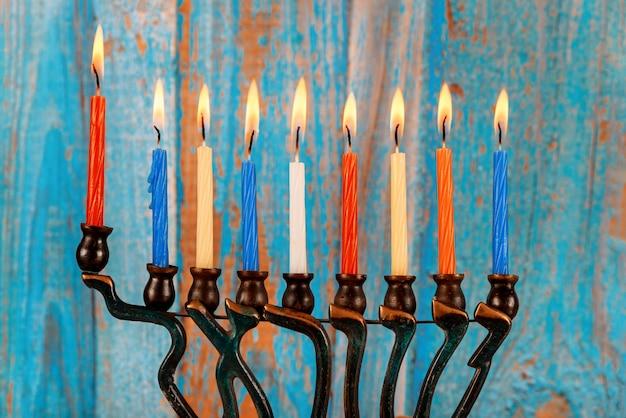 Chanukka-menora mit brennenden farbigen kerzen