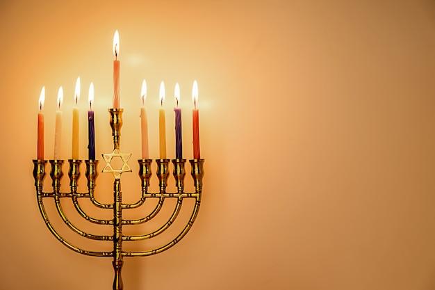 Chanukka-menorah mit brennenden farbkerzen für jüdischen feiertag mit hölzernem hintergrund.