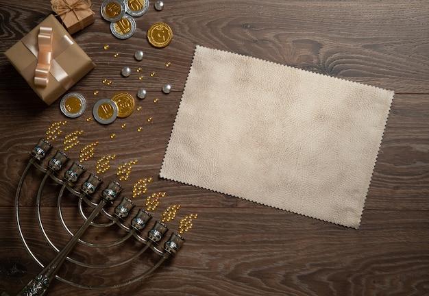 Chanukka schenkt glänzende münzen und süßigkeiten, menora auf einem holztisch. draufsicht