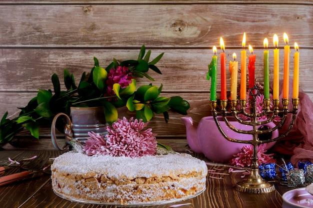 Chanukka süße torte mit brennenden kerzen auf menora