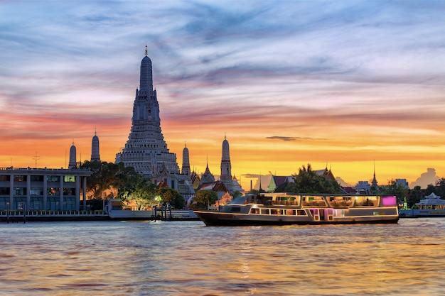 Chao phraya flusskreuzfahrtboot mit tempel der morgenröte, wat arun, bei sonnenuntergang im hintergrund, horizontal